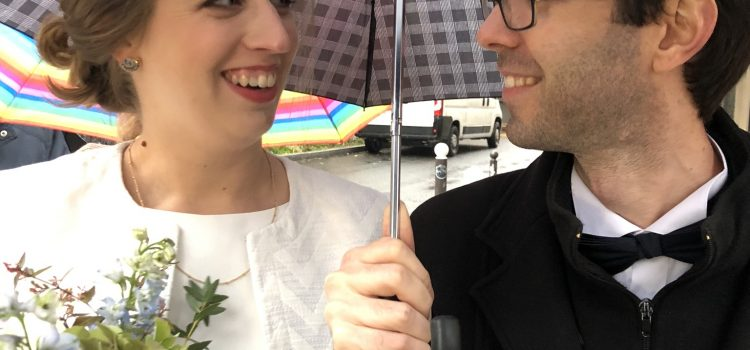 bride and groom under umbrella rainy day wedding