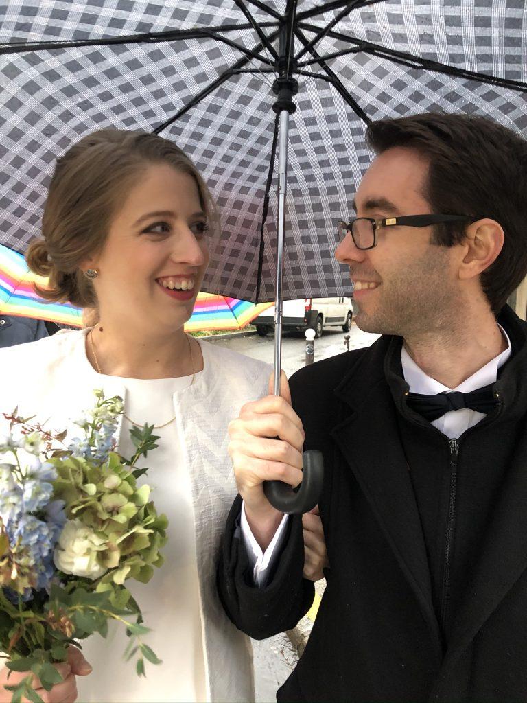 bride and groom under umbrella rainy day wedding