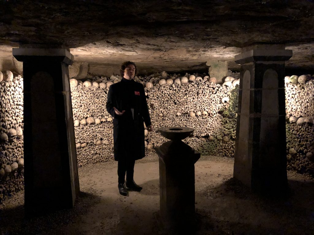 Paris Catacombes tour guide in front of wall of bones