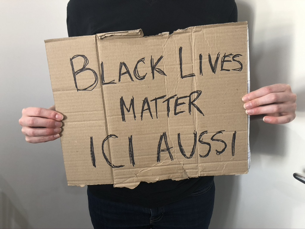 Sign on cardboard: Black Lives Matter Ici Aussi