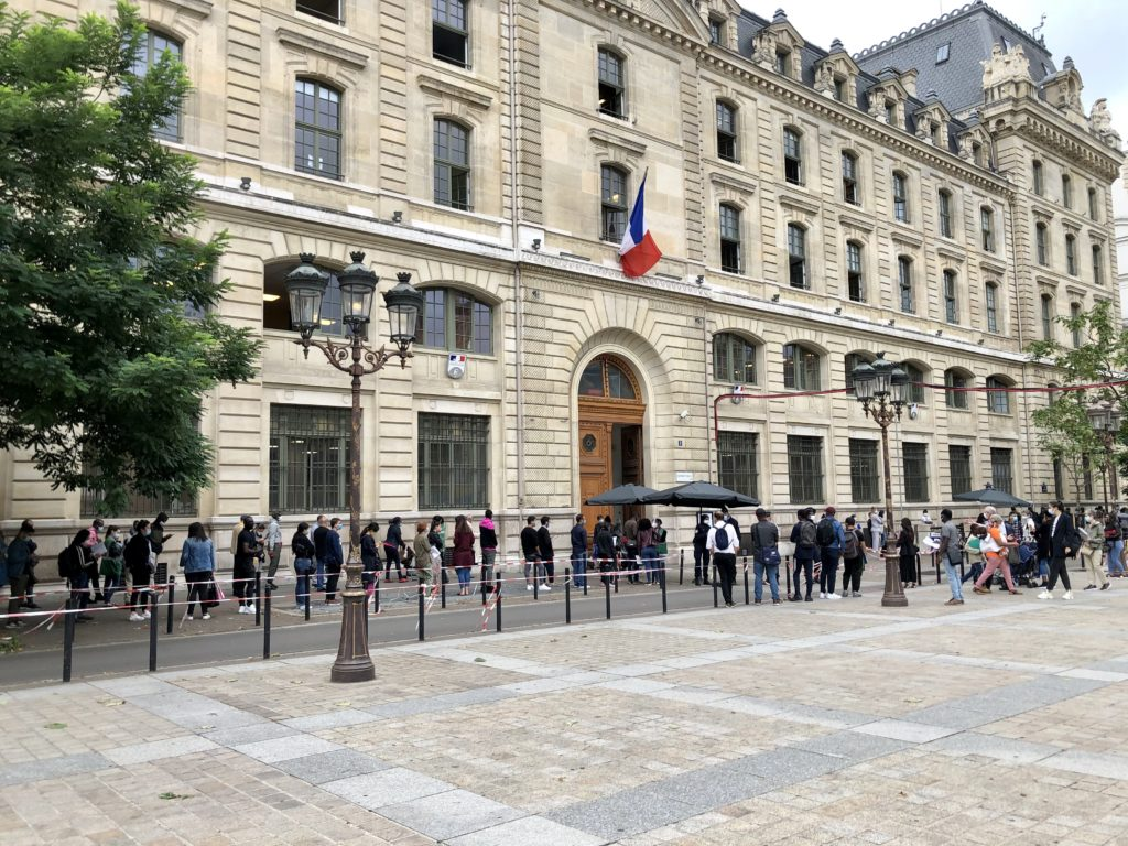 Paris prefecture with long line of people waiting outside