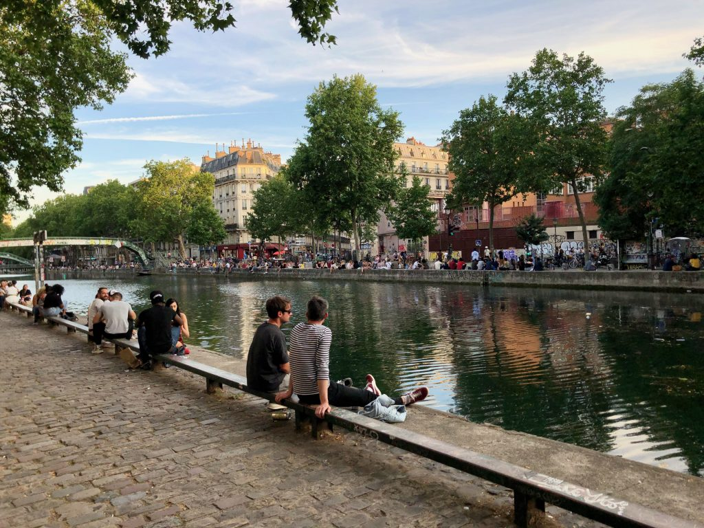 Canal Saint Martin in the summer with groups of people sitting around