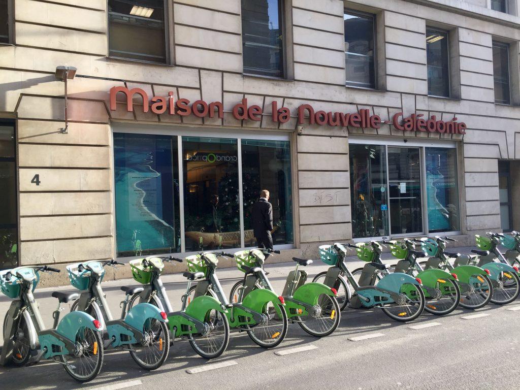 Paris green and blue Vélib city bikes lined up in from of Maison de la Nouvelle-Calédonie