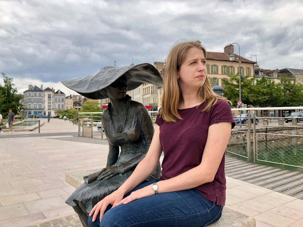 woman sitting next to statue of Lili ou la dame au chapeau in Troyes, France