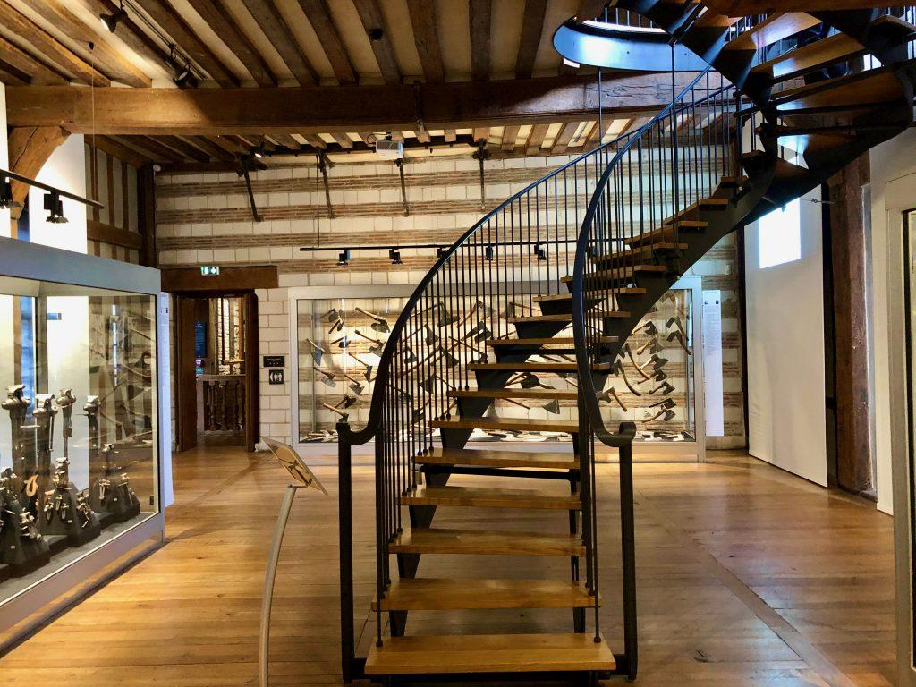 tools on display and staircase inside Maison de l'Outil et de la Pensée Ouvrière in Troyes, France