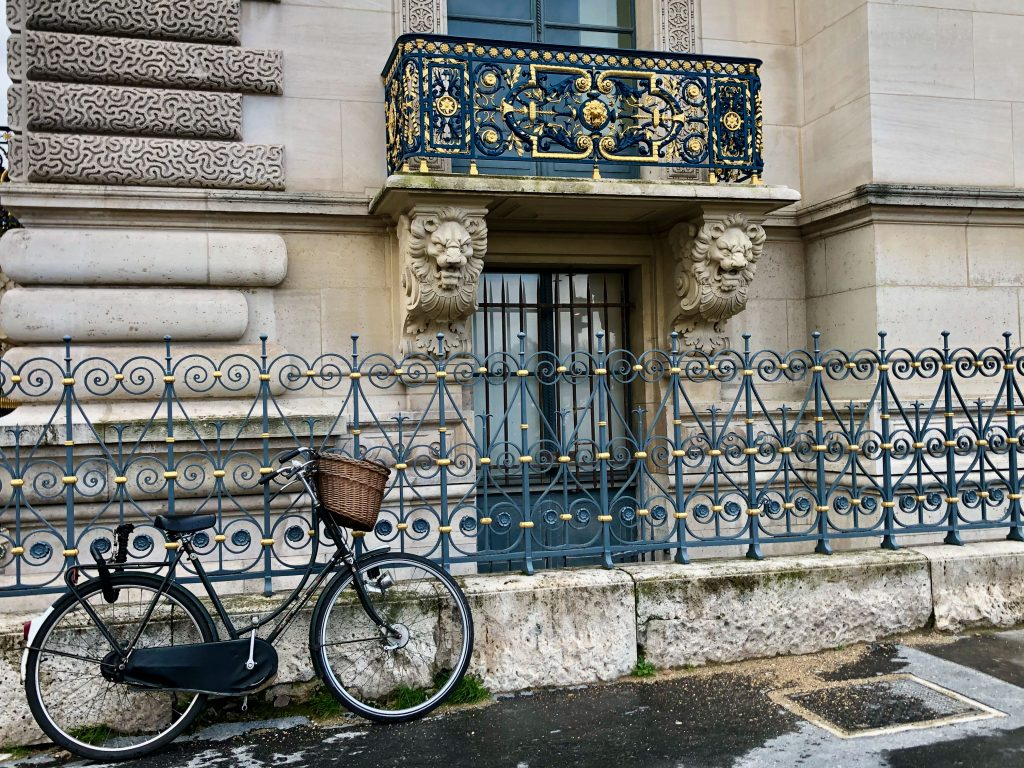 gold detailing on wrought iron railing on a Paris building, bike leaning against a fence