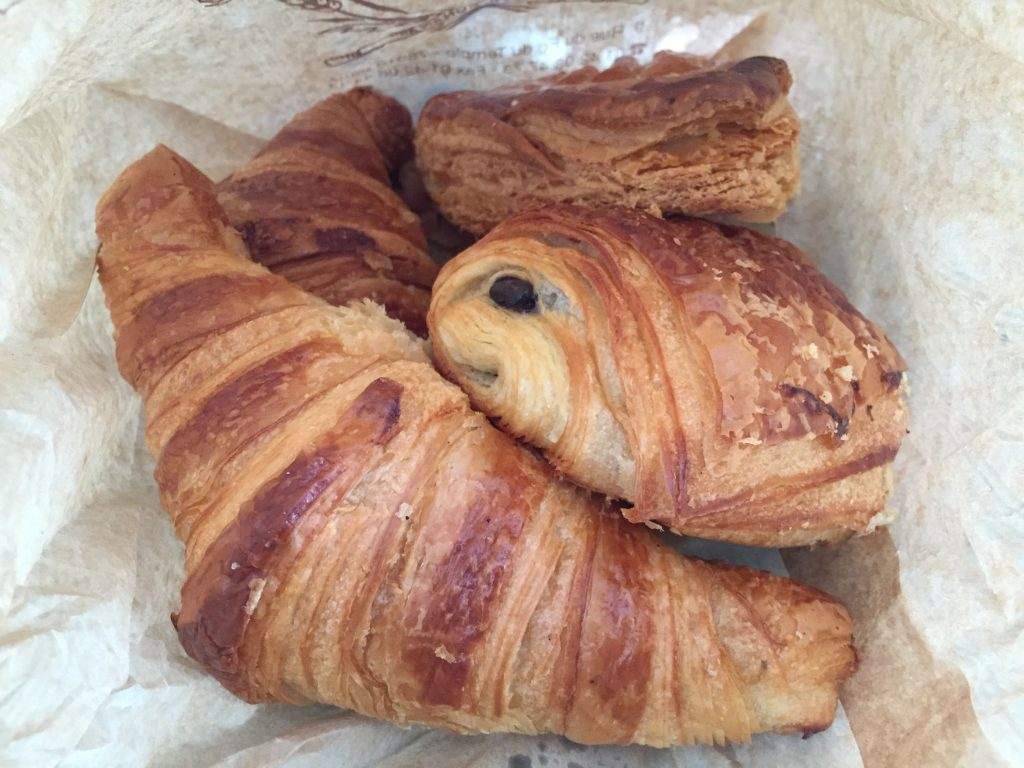croissants and pains au chocolat in a paper bag