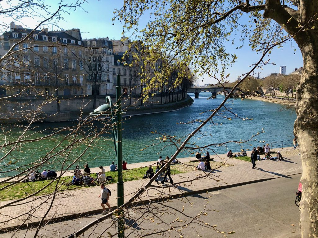 spring day, people sitting on the quai of the Seine River